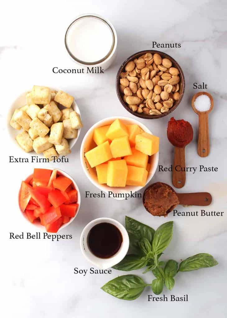 Ingredients for vegan pumpkin curry on a marble countertop