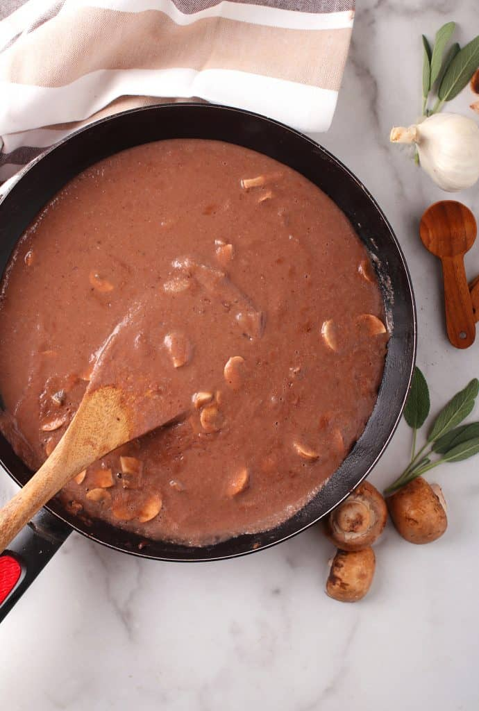 Finished gravy in a skillet with a wooden spoon