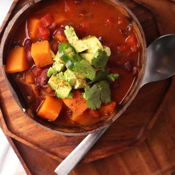 Bowl of finished chili with cilantro and avocado