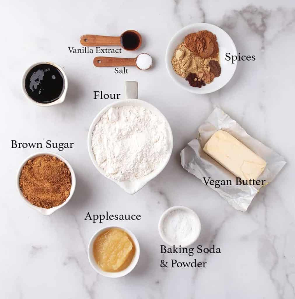 Ingredients for gingerbread cookies measured out and placed on a marble countertop