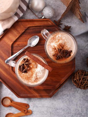 Two glasses of eggnog with whole spices on a wooden platter