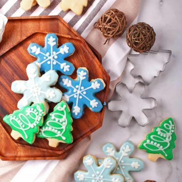 Christmas shaped sugar cookies on a wooden platter