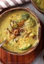 Bowl of homemade broccoli cheese soup on a wooden platter