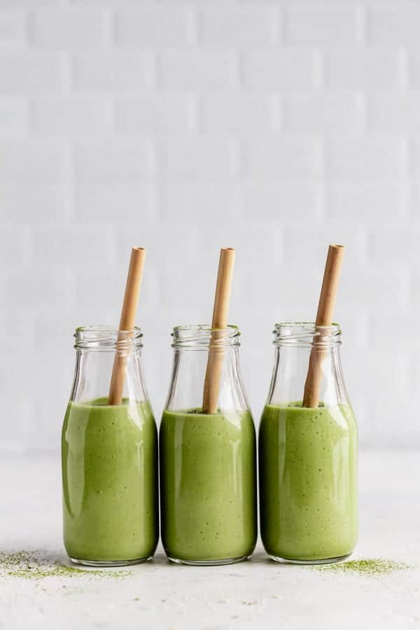 3 glasses of green smoothies with straws