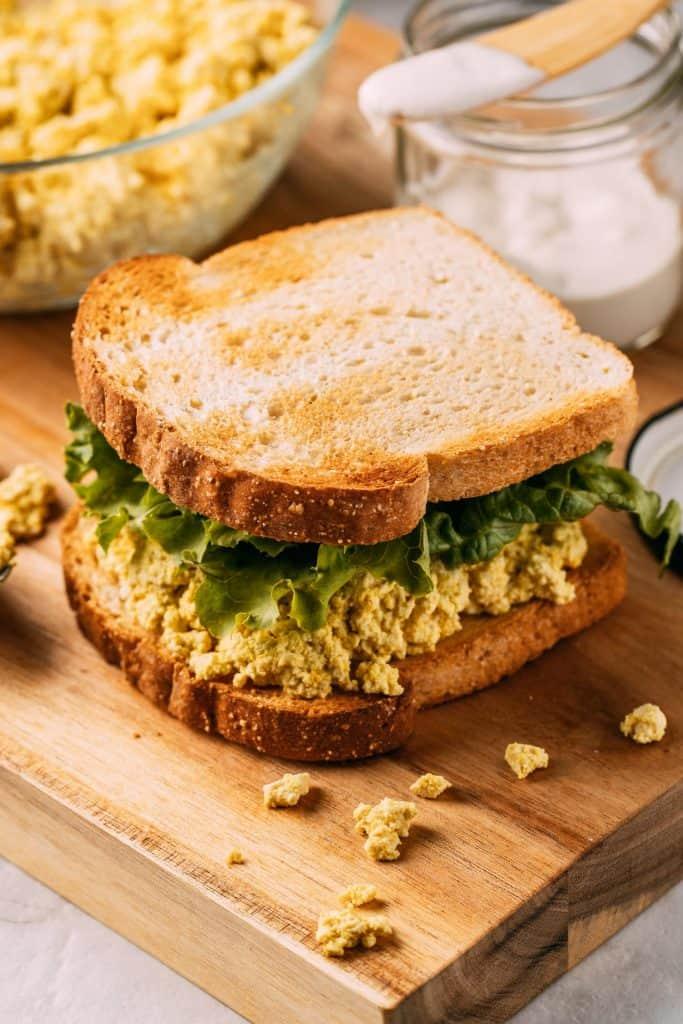 Tofu Egg Salad Sandwich on a wooden cutting board