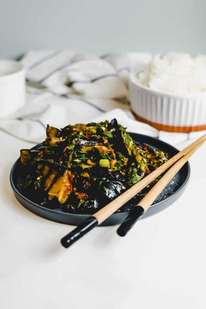 Grilled Chinese Eggplant on a black plate with chopsticks