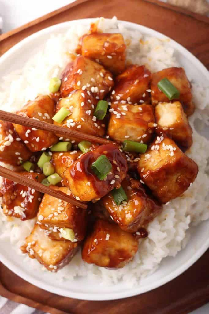 close up shot of general tso's tofu over rice in a white bowl with wooden chopsticks.