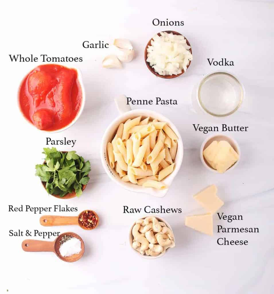 mise en place for penne pasta with vegan vodka sauce - tomatoes, garlic, onions, vodka, penne, parsley, vegan butter, vegan parmesan, red pepper flakes, salt, pepper and raw cashews