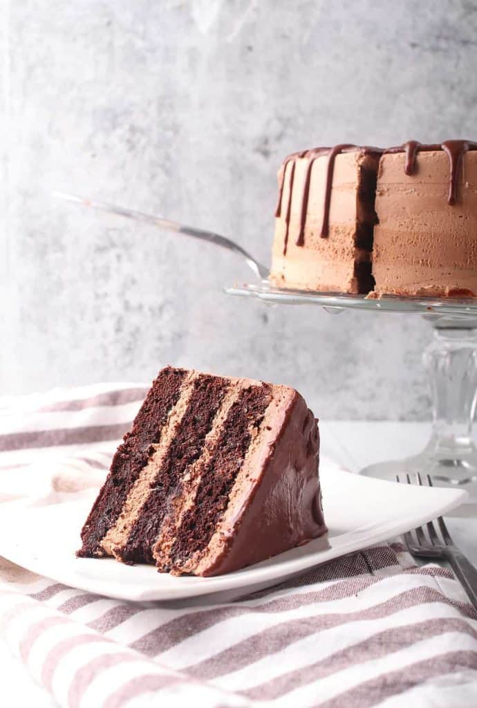 Slice of vegan chocolate cake on a white plate with the whole cake in the background.