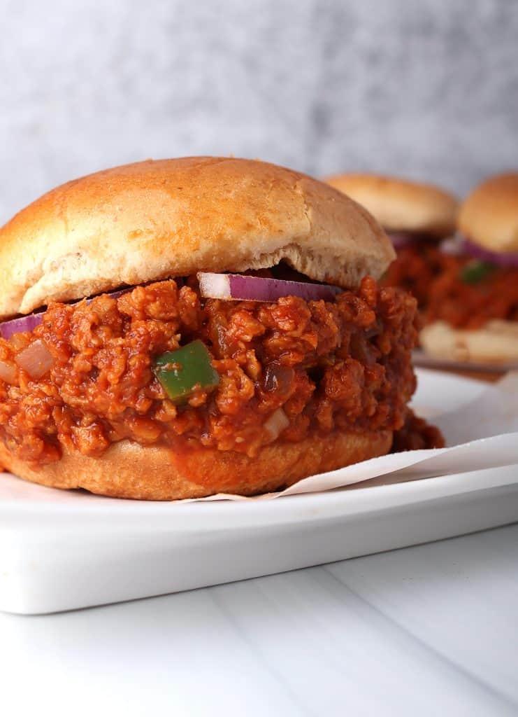 close up shot of homemade vegan sloppy joe on a hamburger bun on a white plate