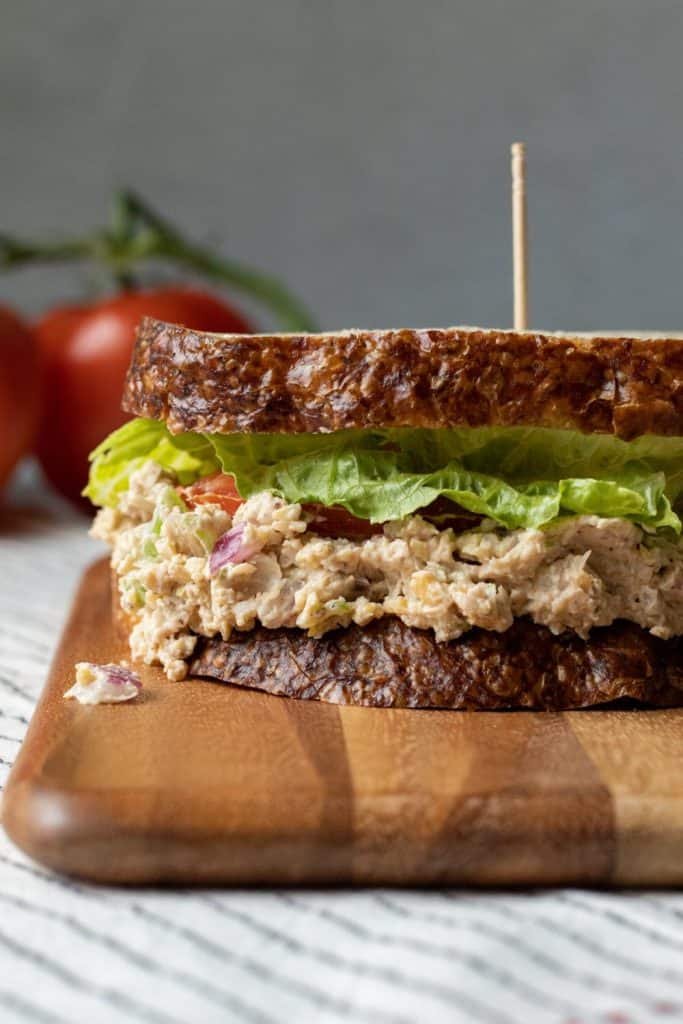 Close up of vegan tuna sandwich on a wooden cutting board