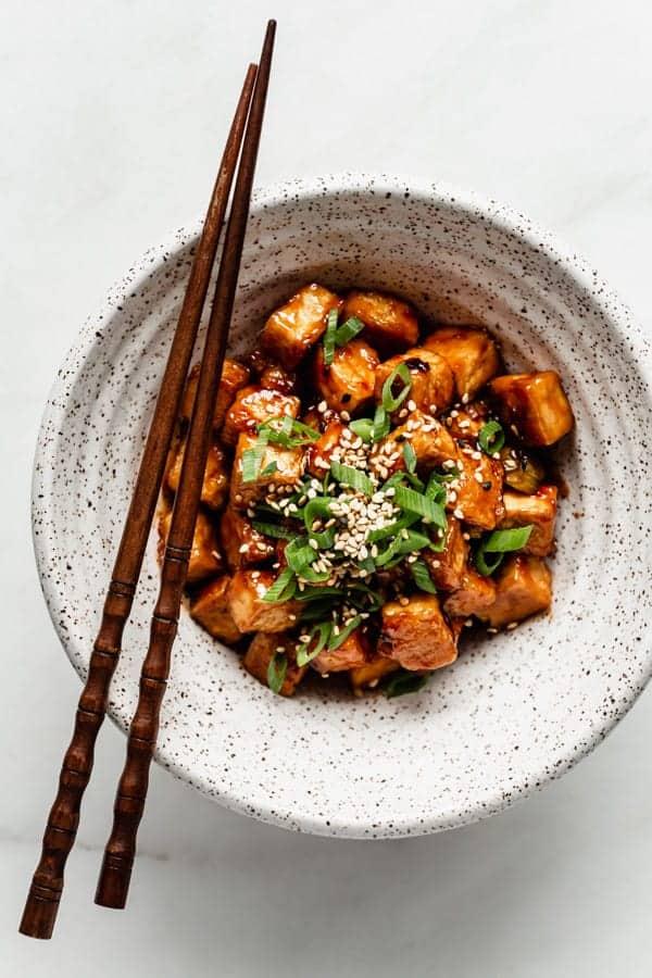 Bowl of General Tso Tofu with chopsticks