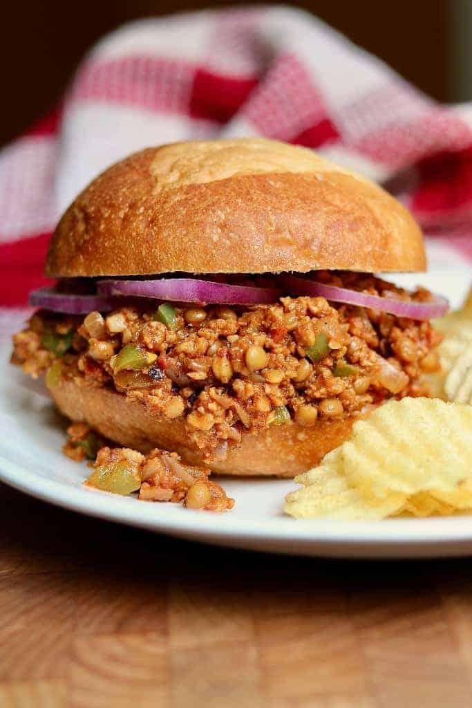 Vegan sloppy joes in a bun with chips on the side