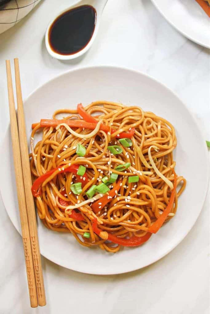 vegan vegetable lo mein on a white plate with chopsticks