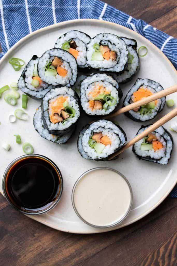 Plate of vegan sushi with dipping sauce and chopsticks