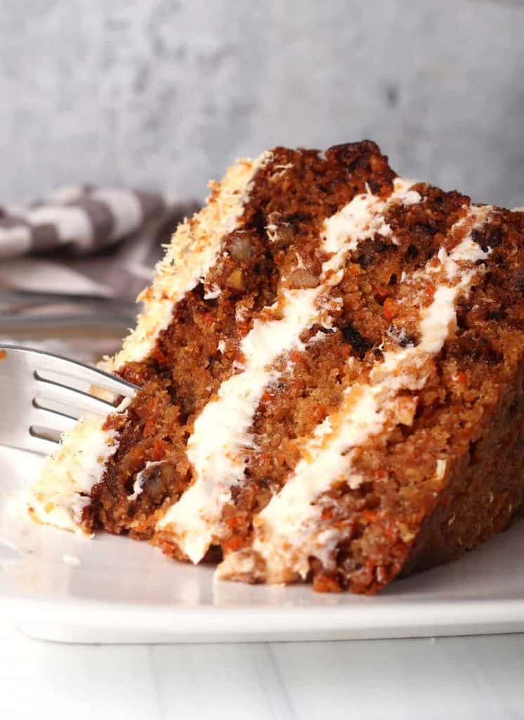 close up of a slice of vegan carrot cake on its side being cut with a silver fork