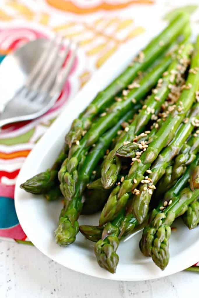 Plate of marinated asparagus stalks with sesame seeds.