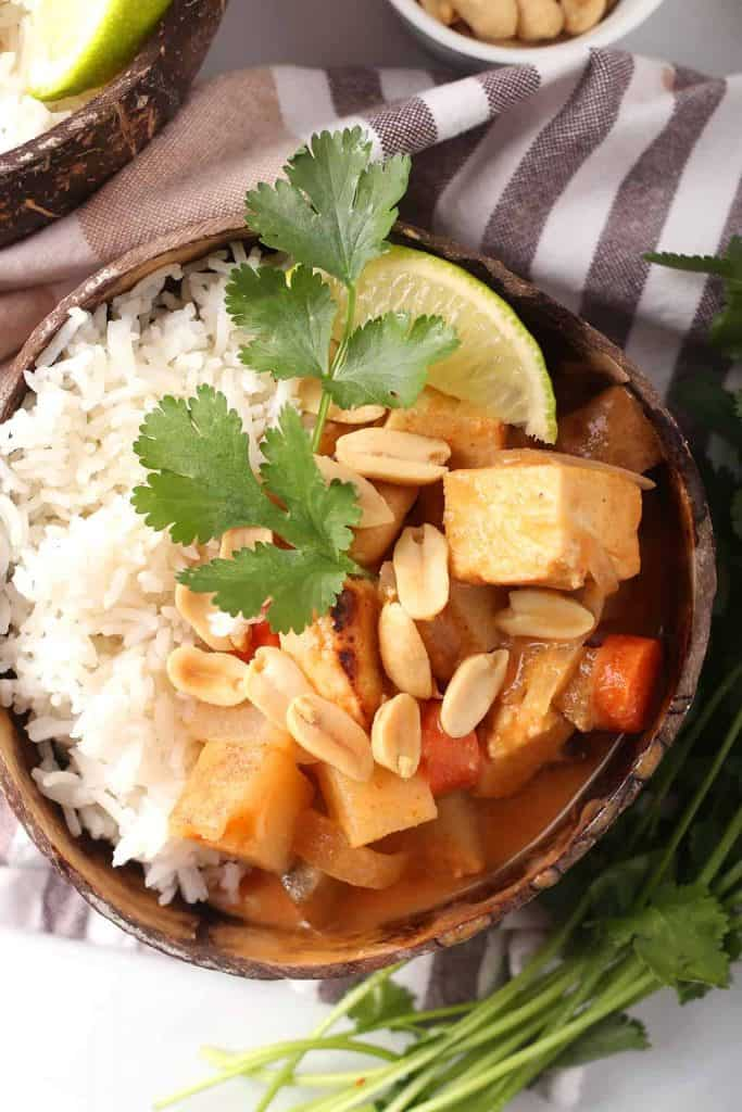 overhead shot of vegan massaman curry with tofu over a bed of rice and garnished with peanuts, cilantro and a wedge of lime