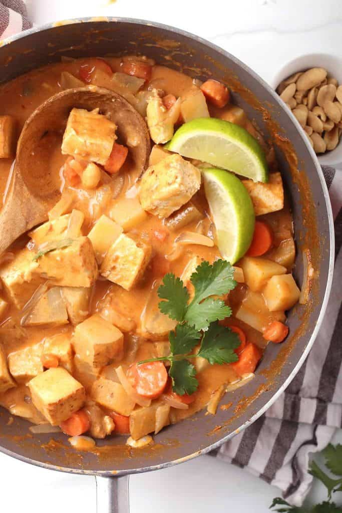 overhead shot of completed vegan massaman curry with tofu in the skillet garnished with fresh cilantro and lime wedges