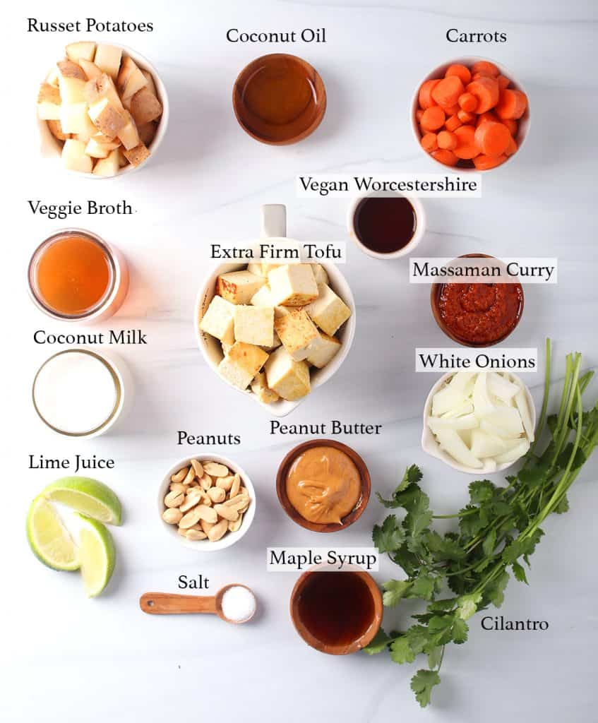 ingredients needed for vegan massaman tofu curry - russet potatoes, coconut oil, carrots, veggie broth, extra firm tofu, vegan worchestershire, massaman curry paste, white onions, coconut milk, peanuts, peanut butter, lime wedges, salt, maple syrup and cilantro