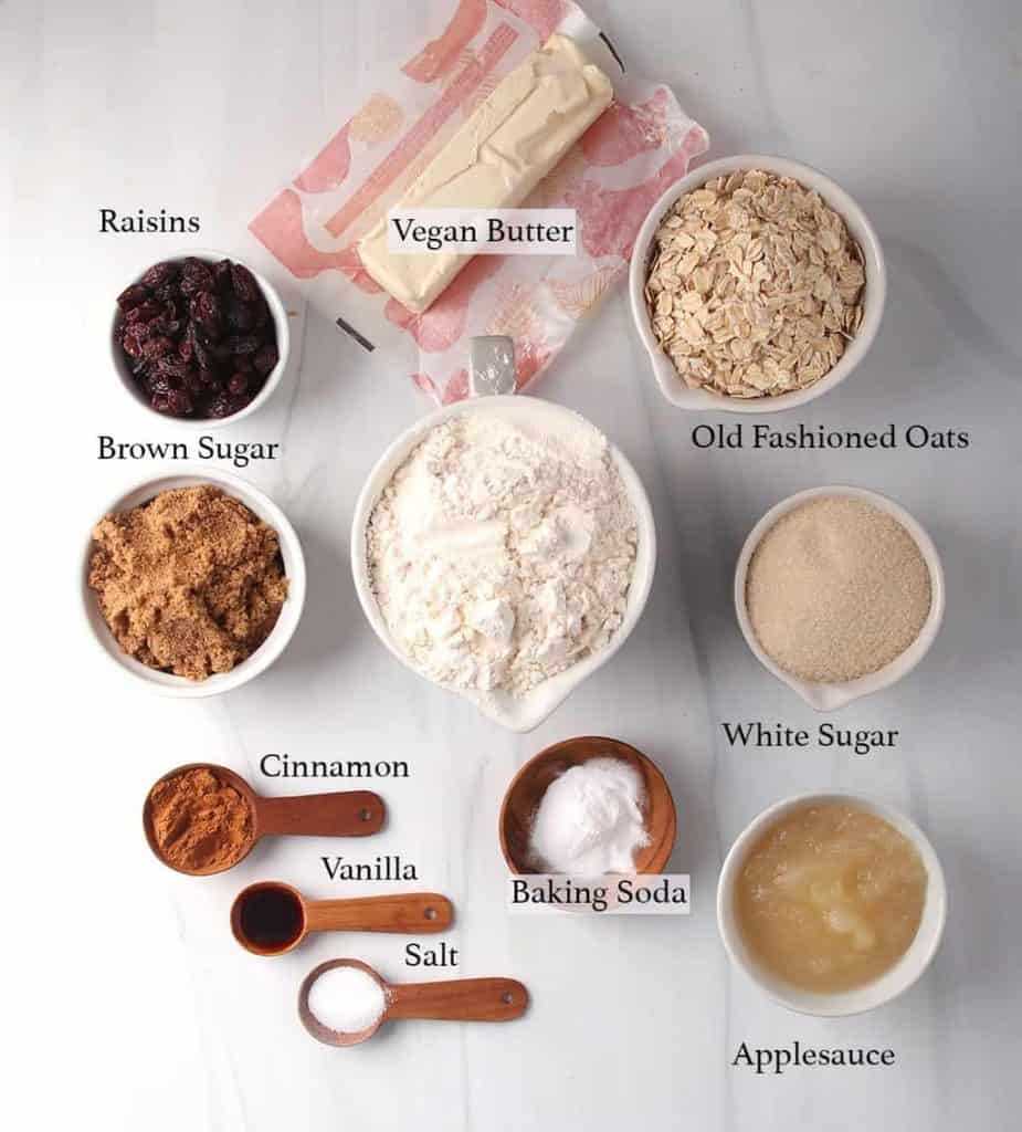 Ingredients for vegan oatmeal raisin cookies measured out and placed on a marble countertop