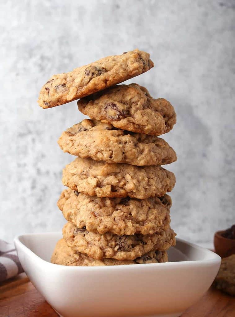 Stack of vegan oatmeal raisin cookies in a small white bowl