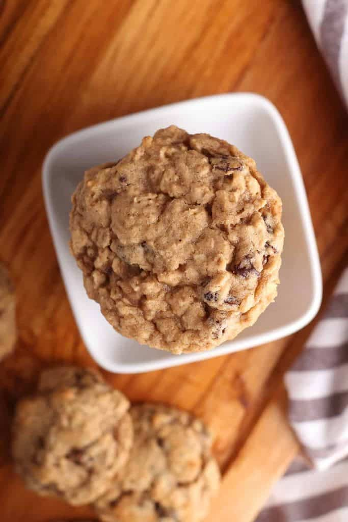 Overhead shot of oatmeal raisin cookies in a white bowl.