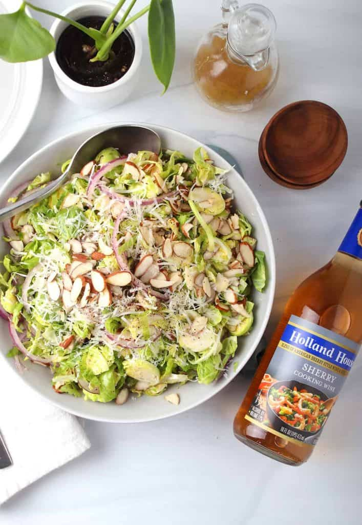 overhead shot of white serving bowl filled with shaved brussels sprouts salad topped with sliced almonds and a bottle of holland house sherry cooking wine on a white table