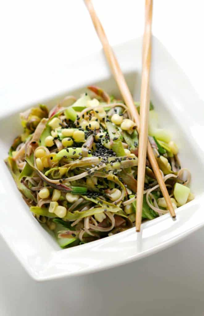 Asparagus and Asian vegetable soba noodles in a white bowl with chopsticks