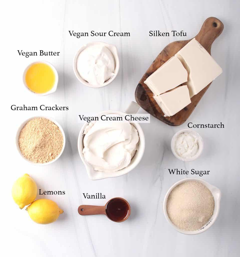 mise en place for new york style vegan cheesecake - melted vegan butter, vegan sour cream, silken tofu, graham cracker crumbs, vegan cream cheese, cornstarch, lemons, vanilla and white sugar in bowls