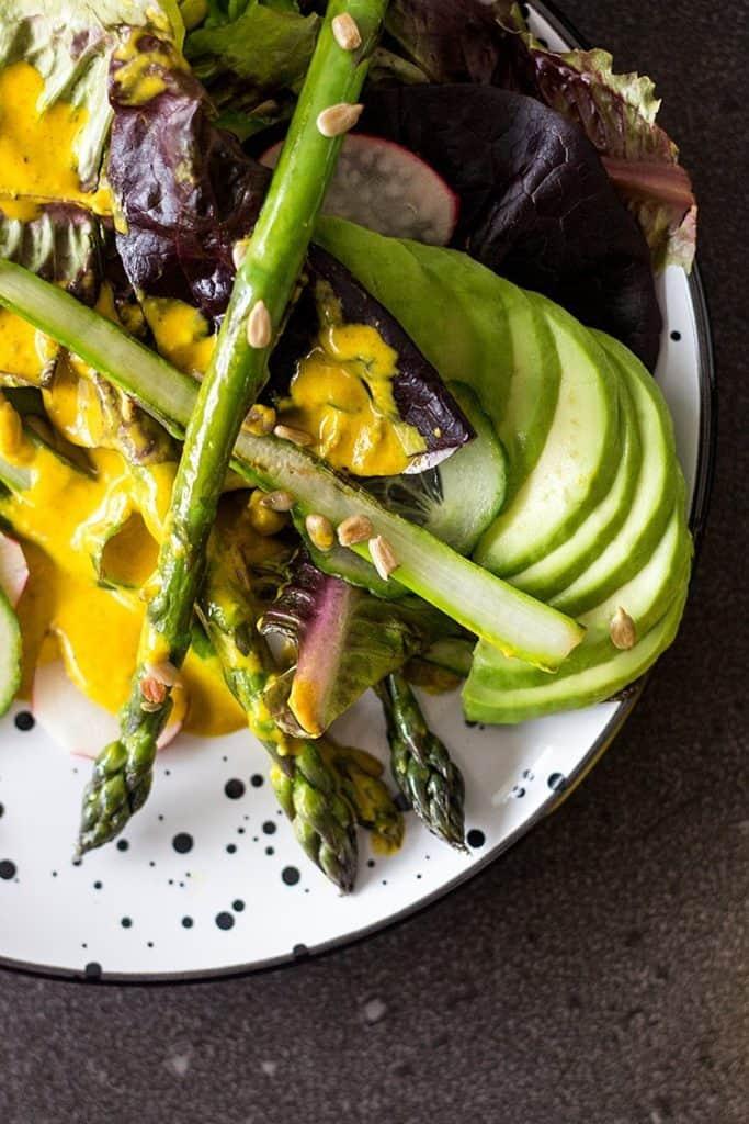 Salad with asparagus, lettuce, avocado, and creamy turmeric dressing.