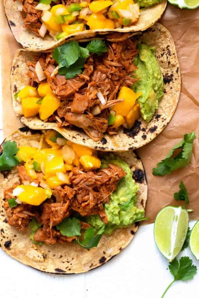 Jackfruit Carnitas tacos with mango salsa on corn tortillas with fresh lime and cilantro
