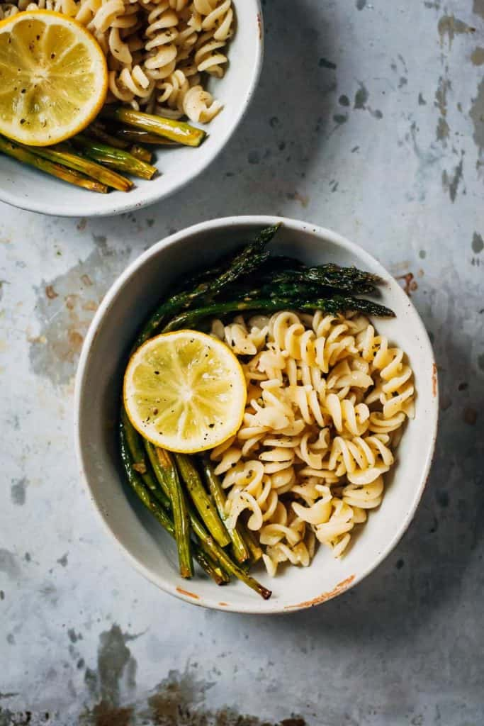 Bowl of lemon pasta and roasted asparagus stalks