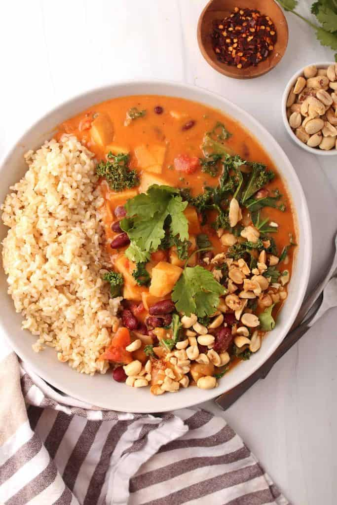 overhead shot of a white bowl of rice and vegan peanut stew garnished with peanuts and fresh cilantro