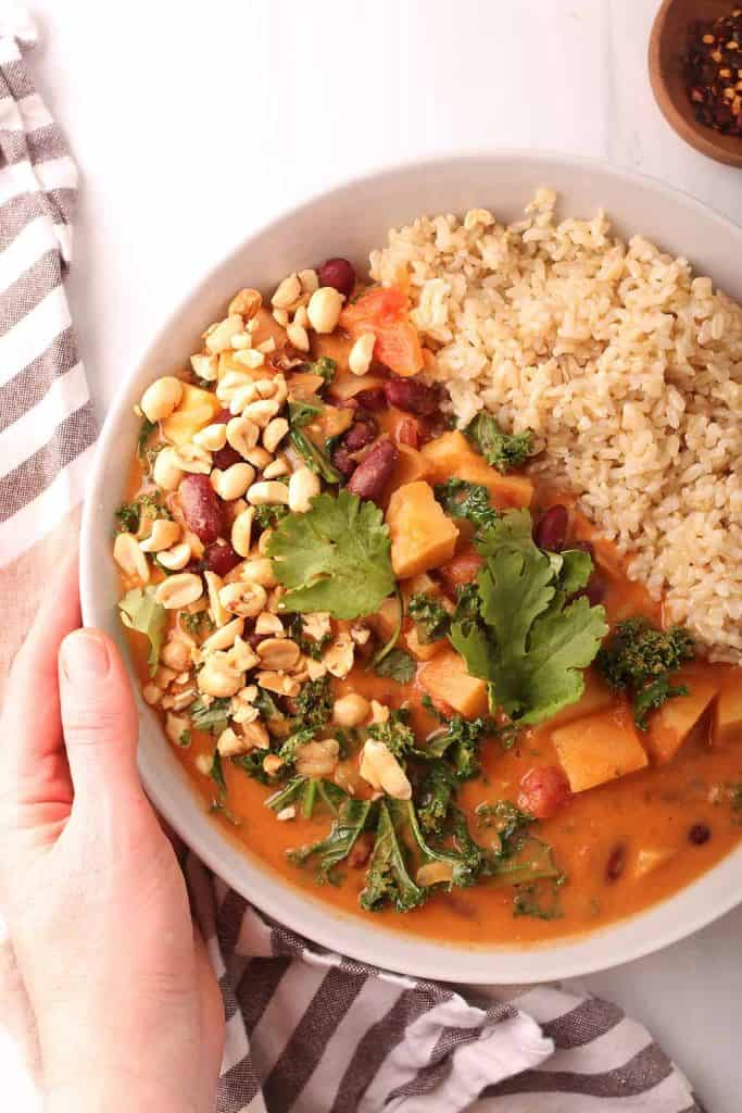 hand holding a white bowl filled with vegan peanut stew and rice