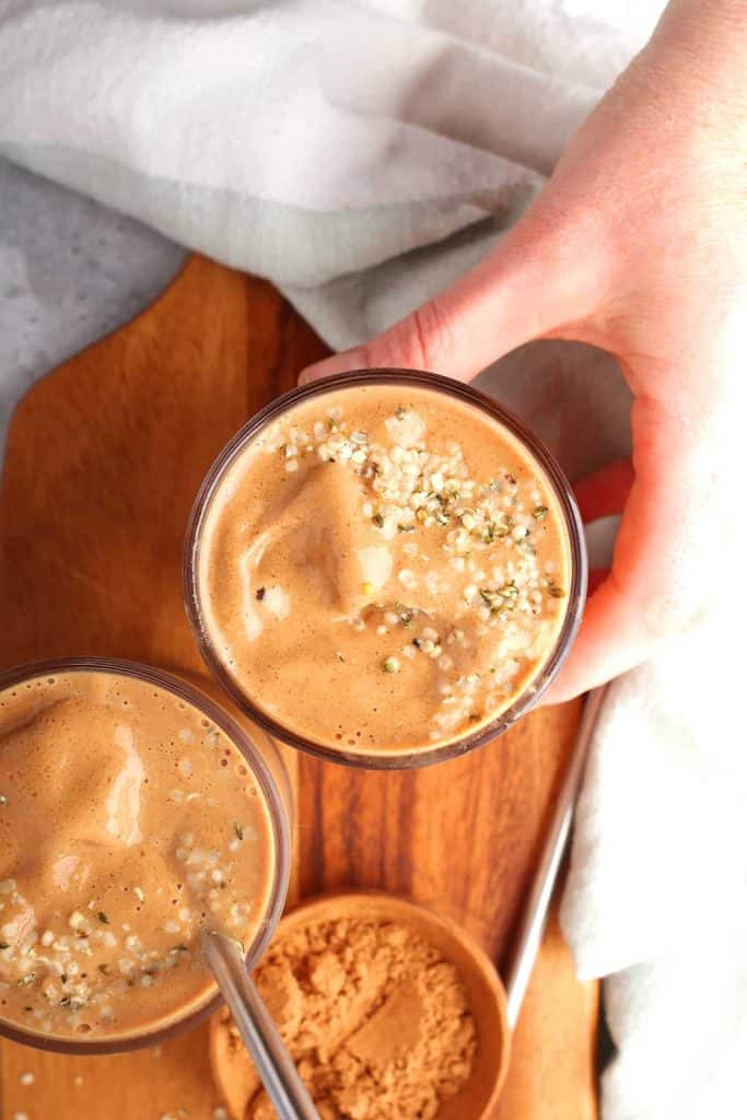 overhead shot of a hand reaching for a glass of chocolate breakfast smoothie topped with hemp hearts