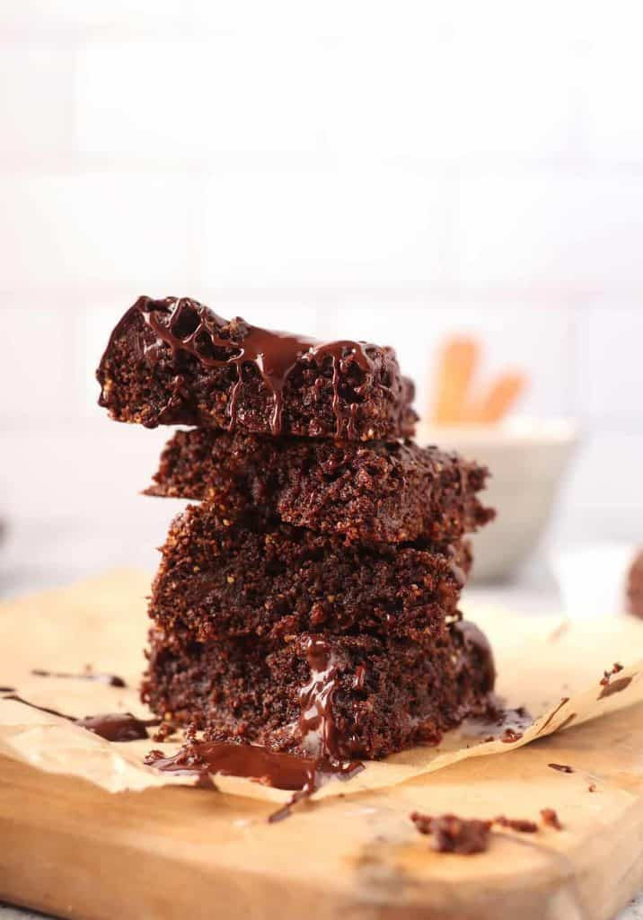 stack of melty gooey vegan gluten free brownies on a piece of parchment paper