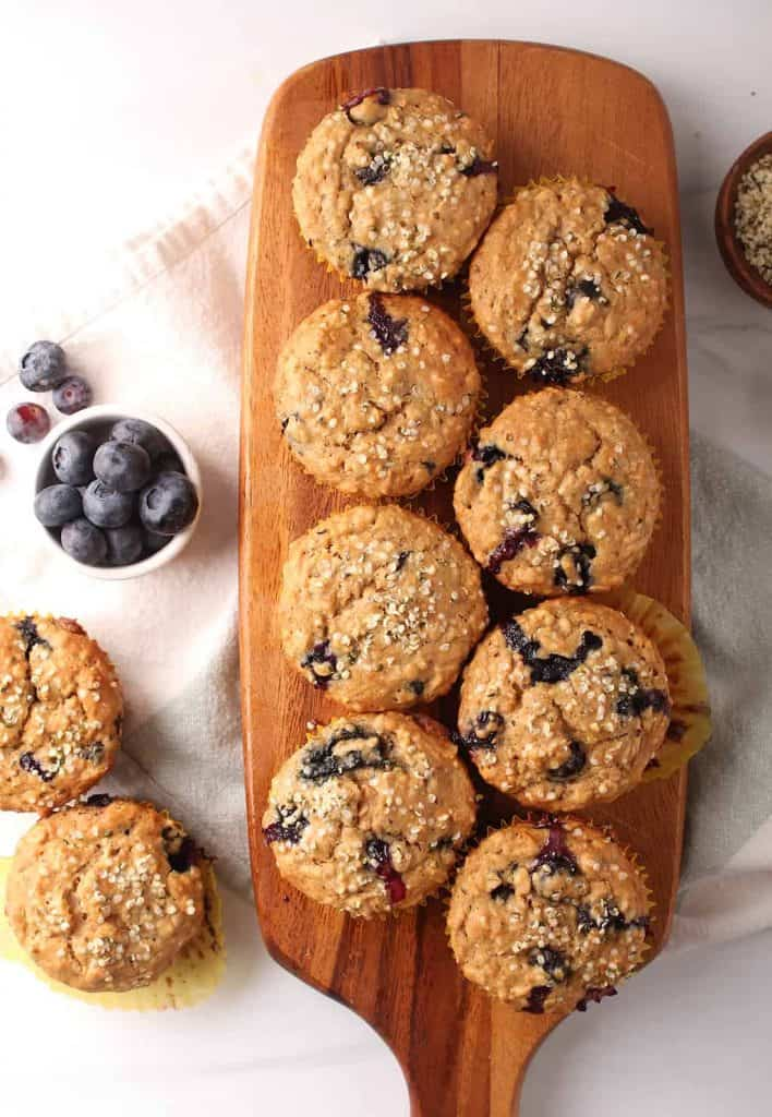 8 healthy blueberry hemp muffins on a wooden cutting board with two off to the side on a white tabletop