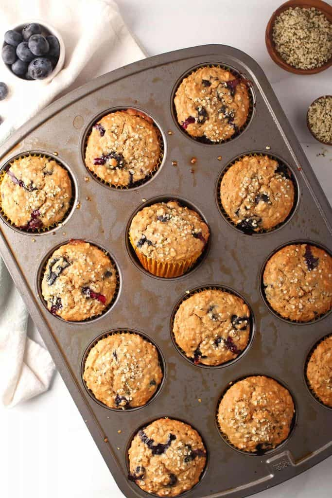silver muffin tin with baked healthy blueberry hemp muffins
