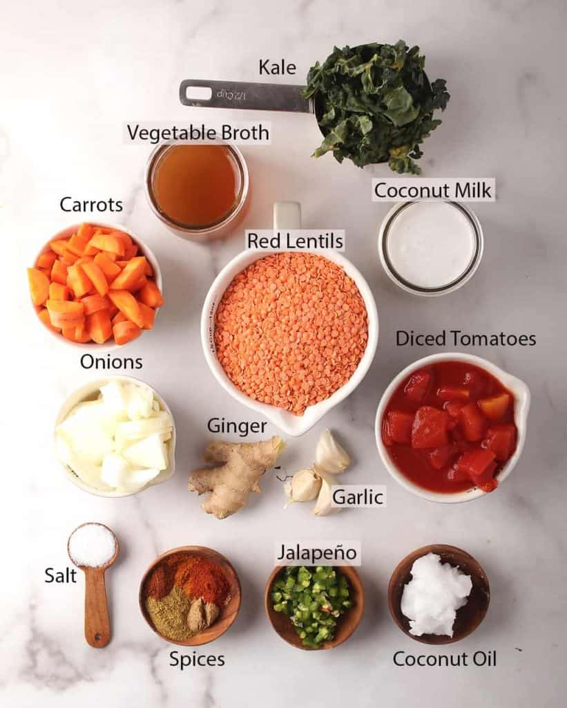ingredients for simple red lentil dahl recipe laid out on a white marble tabletop