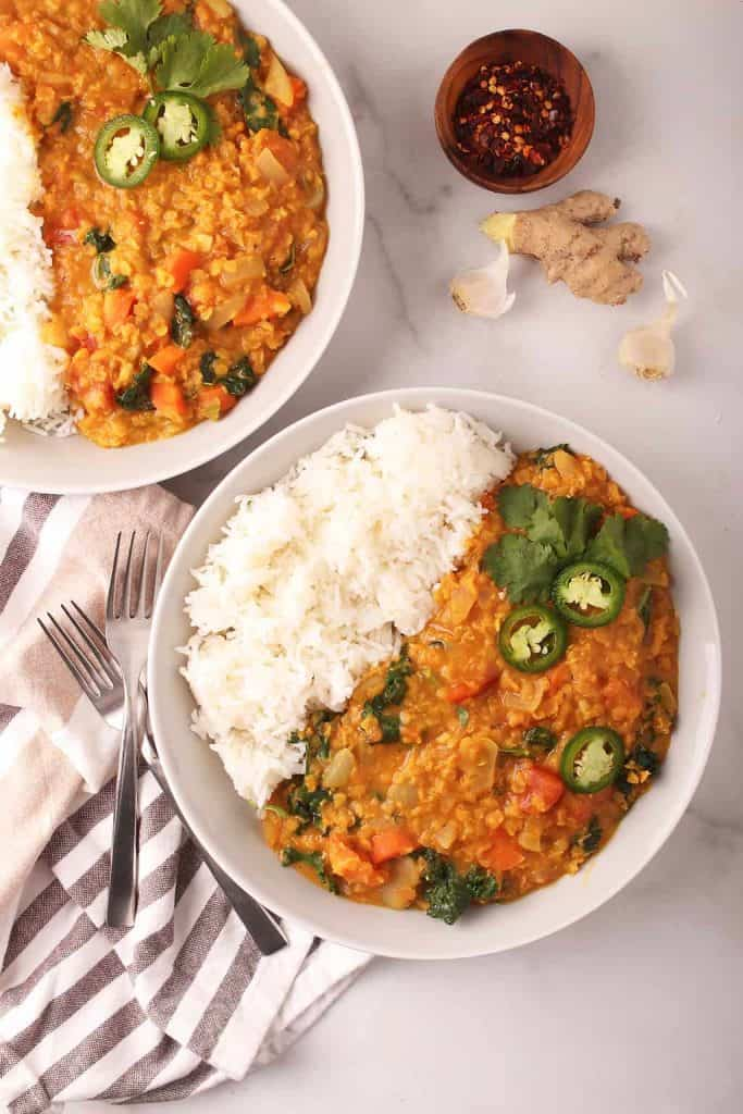 overhead shot of two white bowls filled with long grain white rice and red lentil dahl