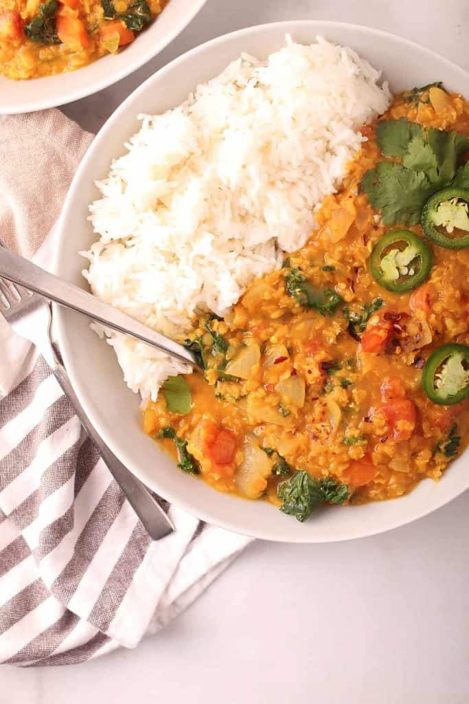 closeup overhead shot of plated red lentil dahl in a white bowl with white rice and a silver spoon