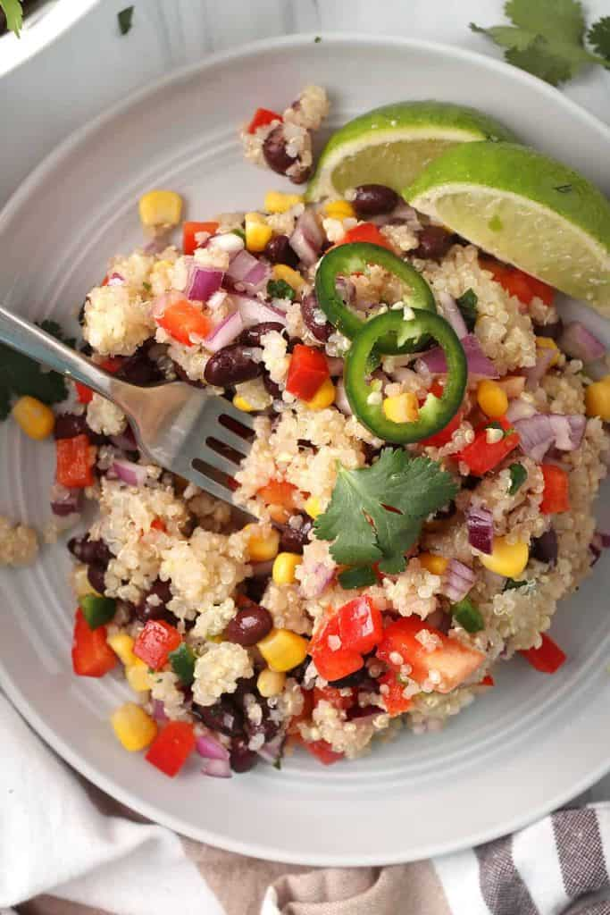closeup overhead shot of southwestern quinoa salad on a white plate with a silver fork