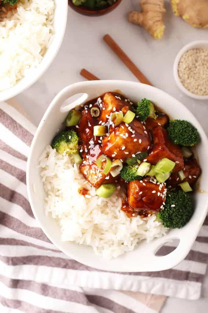 white bowl with sticky rice, teriyaki tofu and steamed broccoli with a grey and white striped towel