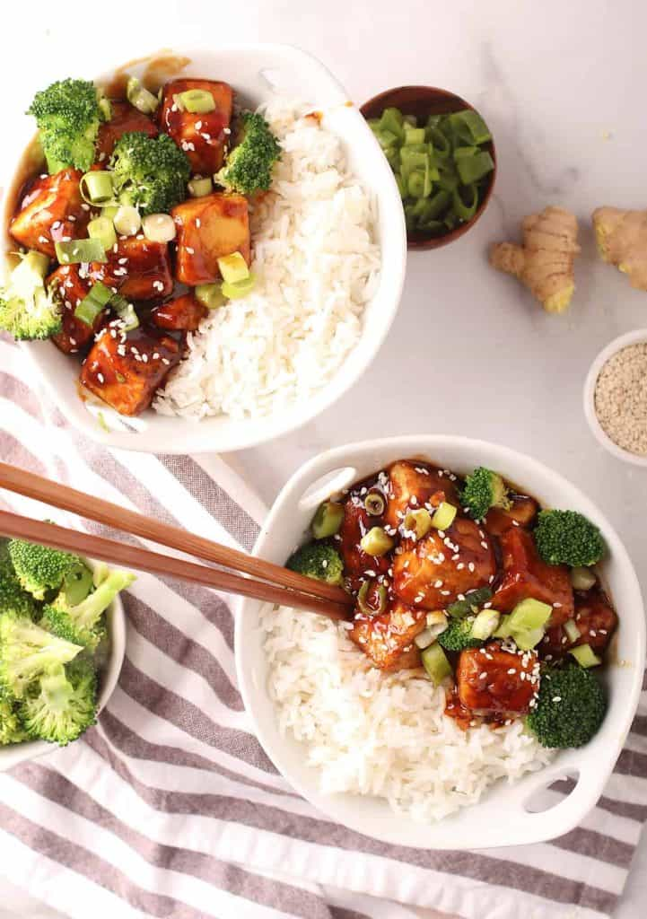 overhead shot of a white bowl with handles filled with steamed rice, teriyaki tofu and steamed broccoli with a pair of wooden chopsticks