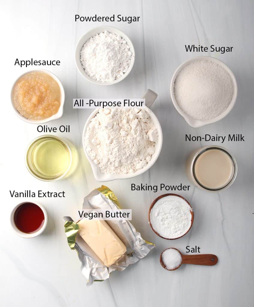 All the ingredients needed for vegan vanilla cake measured out on a white marble background