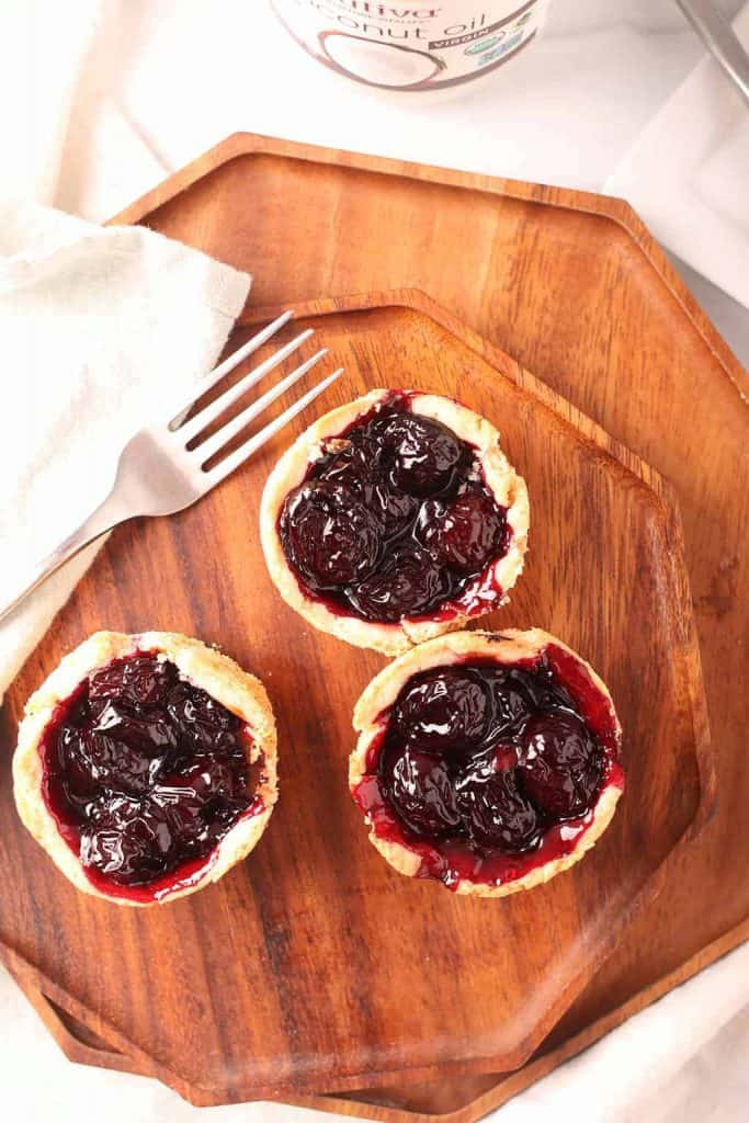 overhead shot of three vegan mini cherry pies on an octagonal wooden plate with a silver fork