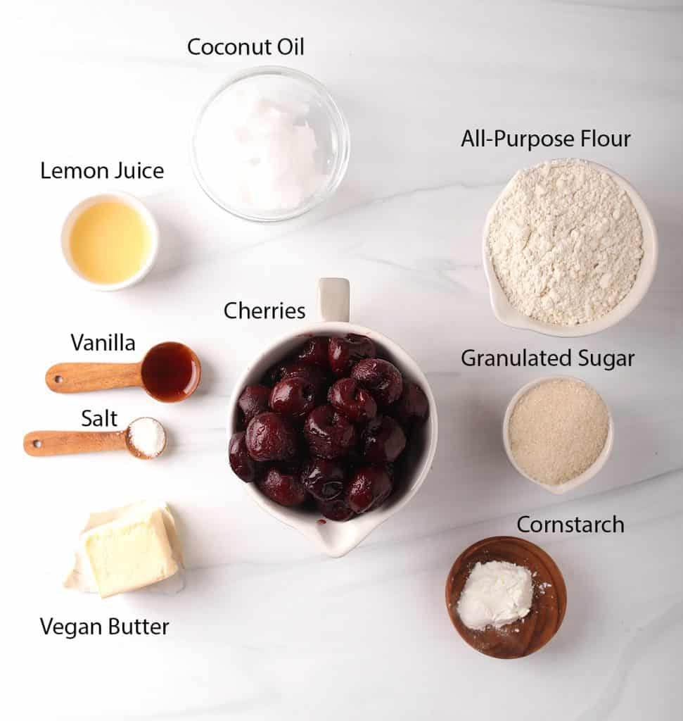 ingredients for homemade vegan cherry pies measured out into bowls on a white table