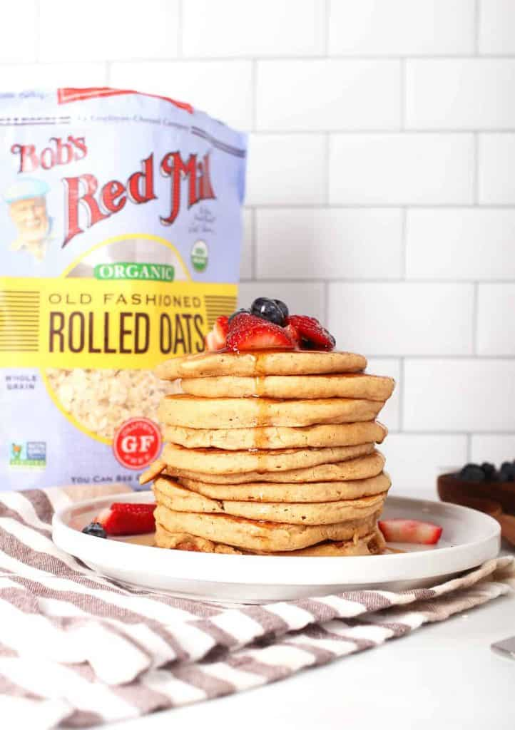 tall stack of vegan oatmeal pancakes topped with berries and maple syrup on a white plate in front of white subway tile
