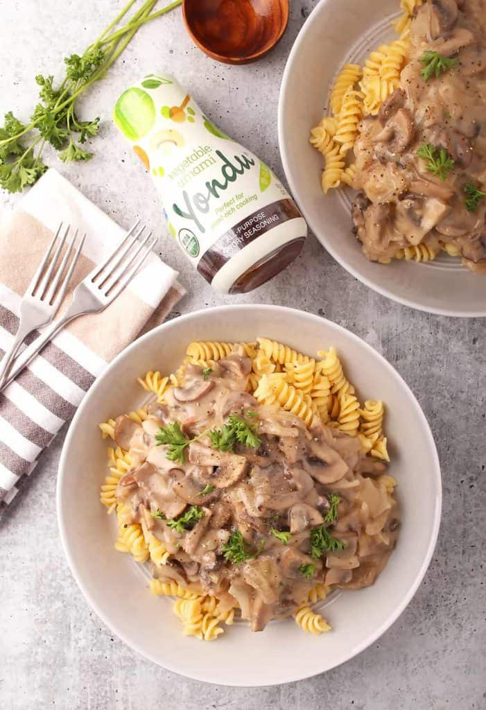 overhead shot of two pasta bowls of vegan mushroom stroganoff on a grey table with a bottle of yondu vegetable umami